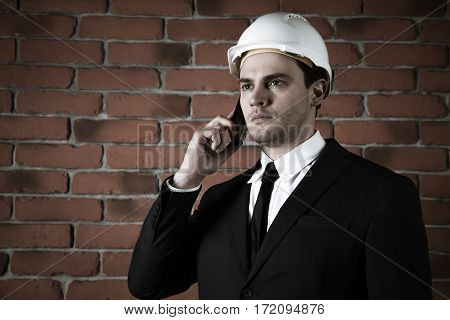 Portrait of a businessman in a helmet with phone in a suit on red brick wall background