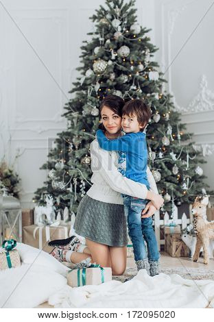 Happy boy with mather near Christmas tree