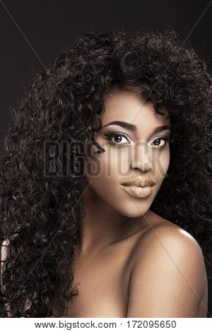 Portrait of beautiful African American girl with dark curly hair. Magnificent eyes, nice make-up. Head and shoulders, indoors, studio