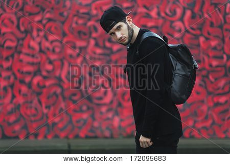 Man standing near colorful wall. Boy in torn jeans, black T-shirt and black cap with rucksack. Turned aside. Looking at camera. Outside