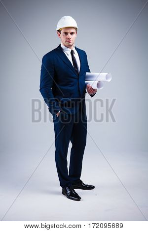 Portrait of a architect in white helmet and in a stylish suit on gray background