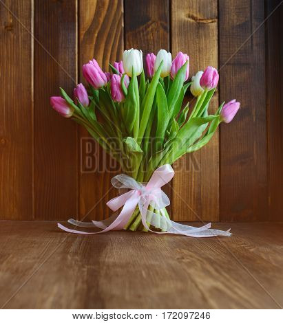 beautiful bouquet with pink and white tulips standing on wooden background