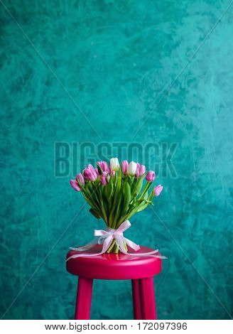 Bouquet of pink and white tulips with pink ribbon on the green painted wall background standing on pink chair. Empty space for text.