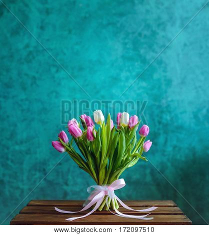 Bouquet of pink and white tulips with pink ribbon on the green painted wall background and empty space for text.