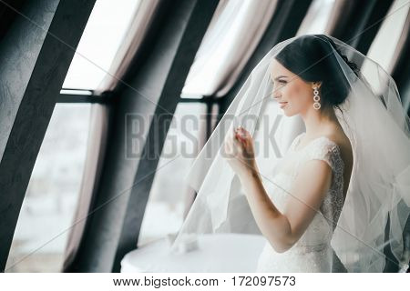 Gorgeous bride with dark hair wearing white wedding dress standing near big window and looking straight, portrait.