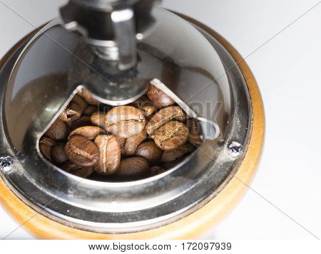 a vintage manual coffee grinder contain of coffee bean before grinding