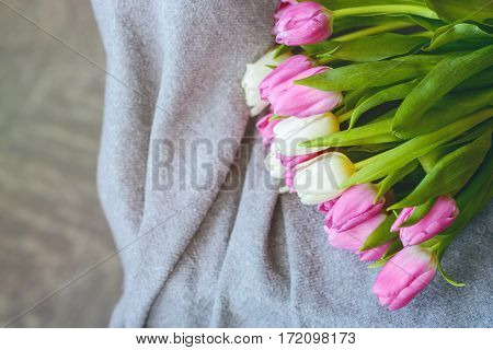 Bouquet of pink and white tulips with pink ribbon on gray blanket