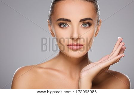 Pretty girl with brown hair fixed behind, clean fresh skin, big eyes and naked shoulders holding a drop of cream, posing at gray studio background, a model with light nude make-up.