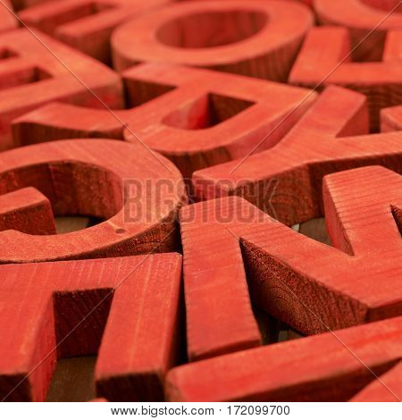 Surface coated with the multiple painted wooden block letters as an abstract backrop composition