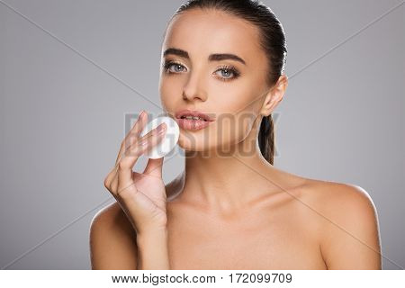 Gorgeous girl with brown hair fixed behind, clean fresh skin, big eyes and naked shoulders holding a cosmetic cleaning sponge, posing at gray studio background.