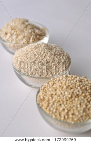 Quinoa in three forms - flour, flakes and grain. Alternative gluten-free grain. Isolated on white