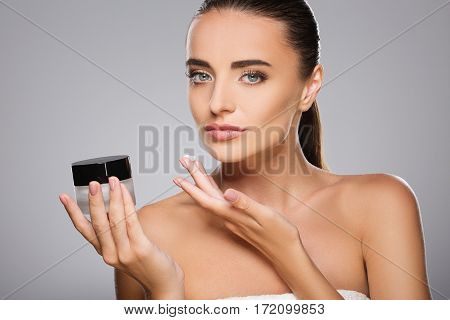Young girl with brown hair fixed behind, clean fresh skin, big eyes and naked shoulders holding a drop of cream, posing at gray studio background, portrait.
