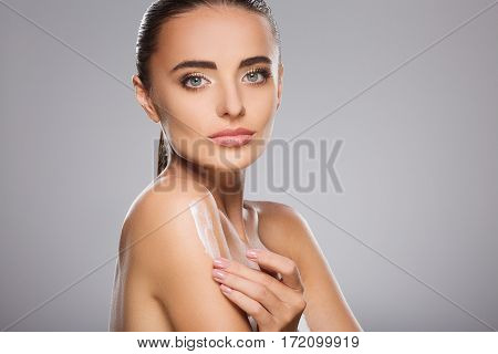 Beautiful girl with brown hair fixed behind, clean fresh skin, big eyes and naked shoulders holding a drop of cream, posing at gray studio background, portrait.