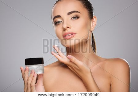 Beautiful girl with brown hair fixed behind, clean fresh skin, big eyes and naked shoulders holding a drop of cream, posing at gray studio background.