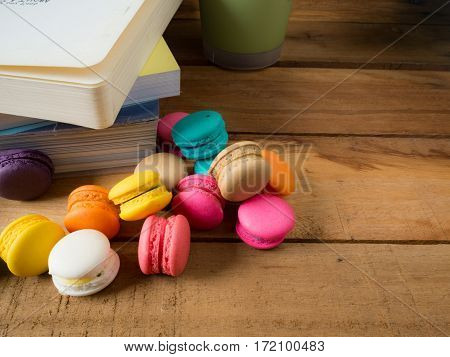 Colorful homemade macaroons staying on open book over valentines day concept.
