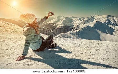 Happy woman relaxing on the top of mountain under blue sky with her camera at sunny winter day, travel vacation, landscape mountains background.
