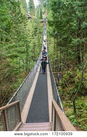 Vancouver Canada - January 28 2017: Many sightseers make their way across the Capilano Suspension Bridge.