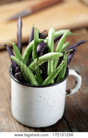 Green and purple string bean in the vintage mug