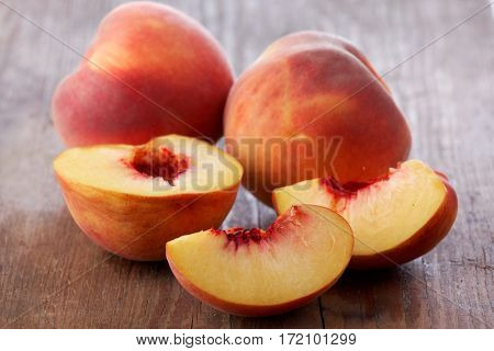 Sliced and whole peaches on a rustic table closeup