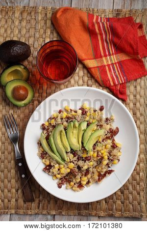 Quinoa and vegetables salad with avocado on a rustic table