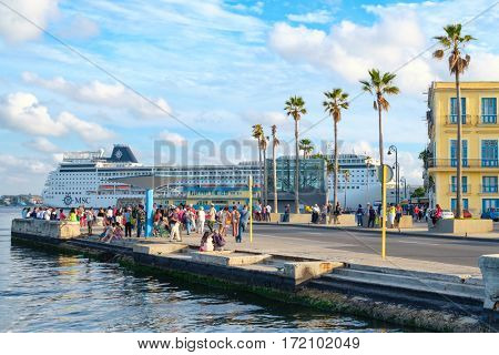 HAVANA,CUBA - FEBRUARY 15,2017 : Street scene in Old Havana with colorful colonial buildings and a modern cruiser ship on the background