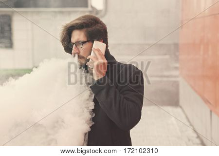 Young hipster man with a beard and glasses smokes an electronic cigarette. He says on the cell phone. Youth fashion. Delicious pairs. Cloud of steam. Business meeting