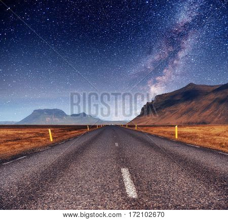 Fantastic starry sky and the milky way. Bridge over a channel connecting Jokulsarlon Lagoon and Atlantic Ocean in southern Iceland.