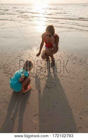 Mother and baby girl drawing on sandy beach.