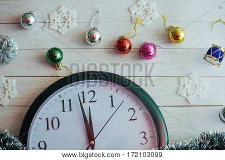 New Year Midnight - clock on background wooden background and Christmas balls. Greeting card. In anticipation of the holiday