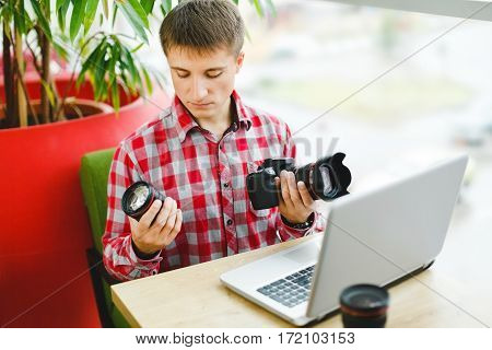 Attractive young man sitting in cafe with laptop and choosing professional camera, photographer, portrait.