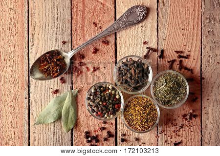 Assortment of spices in glass bowls and spoon on wooden background