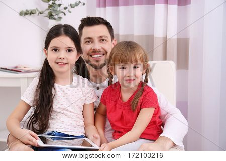 Father with daughters on sofa in the room