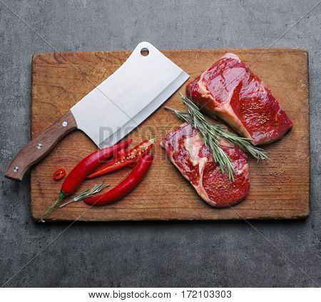 Raw steak with spices on cutting board