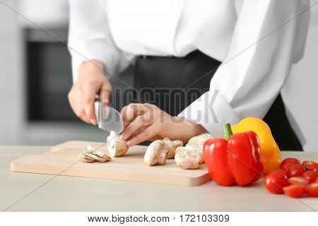 Female chef cutting mushrooms on wooden board closeup