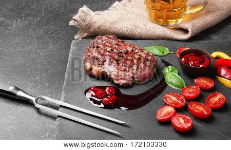 Tasty juicy steak with spices and sauce on slate plate