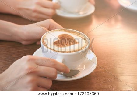 Female hands with cup of hot tasty coffee in cafe, close up view