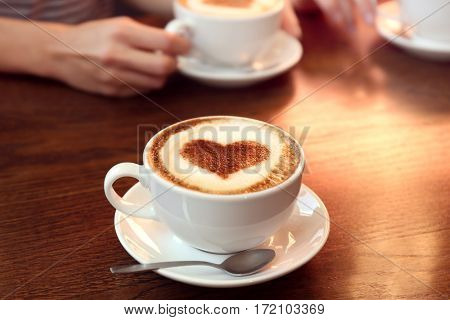 Cup of hot tasty coffee on wooden table, close up view