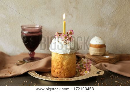 Easter cake with lighted candle on metal tray