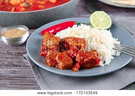 Portion of chicken tikka masala with rice in plate on grey wooden table