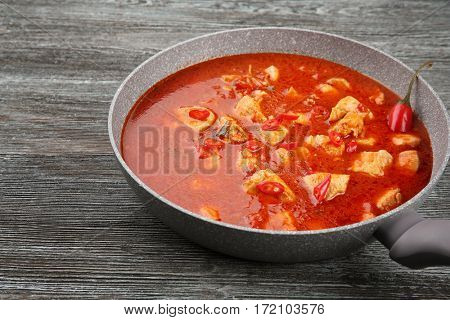 Chicken tikka masala in pan on grey wooden table