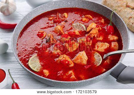 Chicken tikka masala in pan on white wooden table