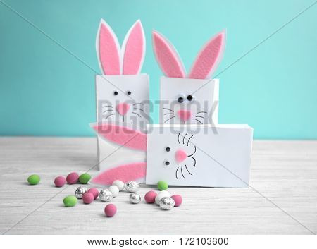Easter decorative bunny bags with candies on wooden table