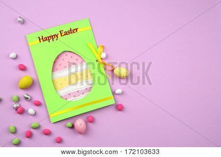Easter concept. Greeting card and colourful eggs with candies on purple background