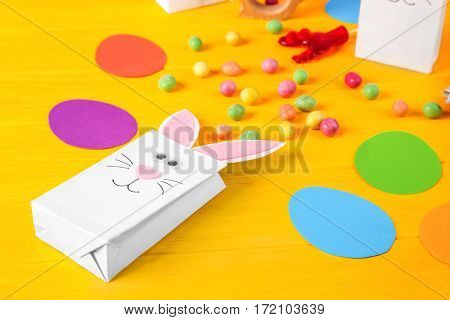Easter decorative bunny bag with candies on wooden background