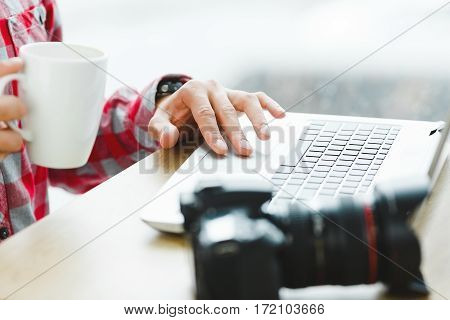 Man's hands holding a cup of coffee and working in internet with laptop, professional camera on table, close up.