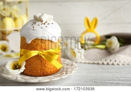 Decorative plate with Easter cake on wooden table