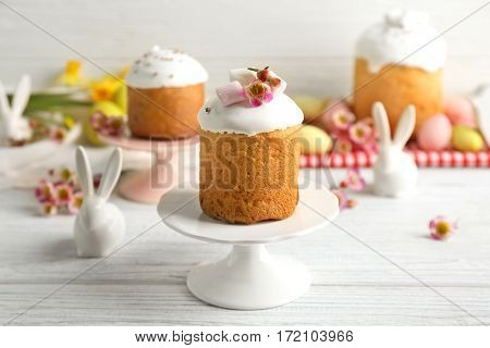 Stand with Easter cake on wooden table