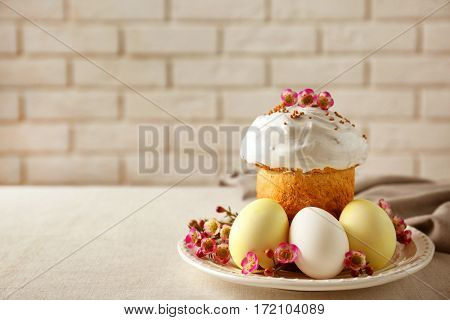 Plate with sweet Easter cake and eggs on table