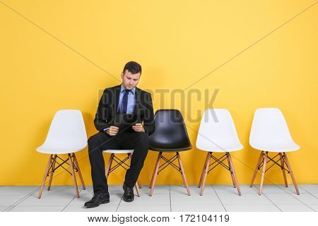 Young man waiting for job interview on yellow wall background