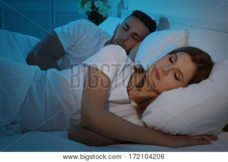 Young cute couple sleeping together in bed